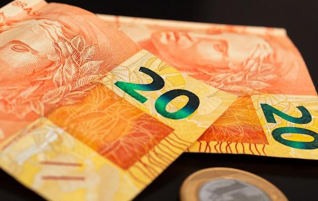 Billets d'argent réel brl brésil et une vraie pièce de monnaie en photographie close up avec fond noir