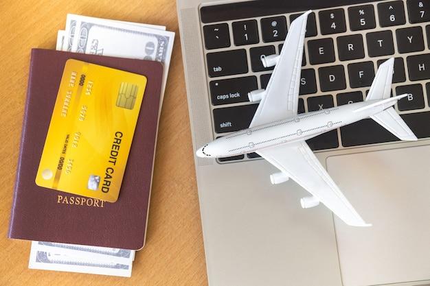 Billets d'avion, passeports et carte de crédit près d'un ordinateur portable et d'un avion sur la table.
