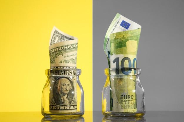 Billets de banque en dollars américains et en euros dans des bocaux, divisés par arrière-plan différent.