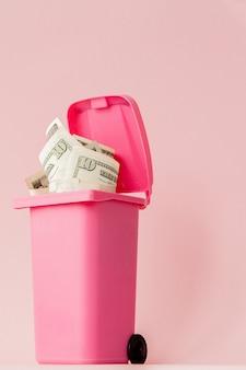 Billets de banque en dollars dans la poubelle rose sur fond rose.