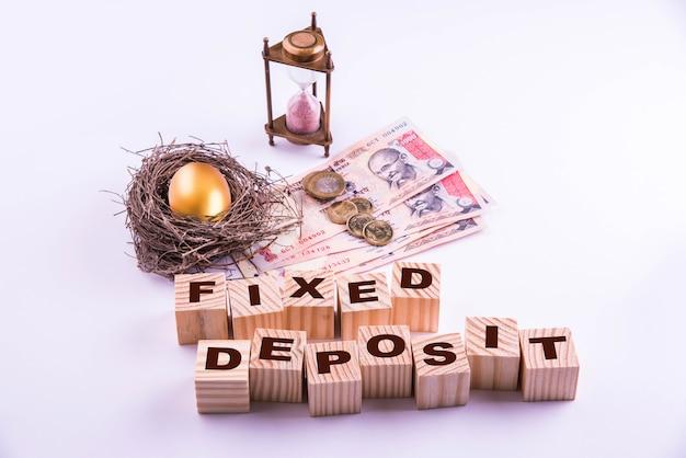 Des billets de banque indiens avec des pièces de monnaie et des œufs d'or ainsi qu'une horloge de sable antique et des blocs de bois avec des fonds communs ou un dépôt fixe écrit dessus