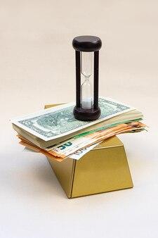 Les billets de banque sur lesquels il y a une horloge de sable contre un lumineux