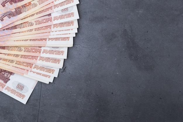 Billets de banque russes de cinq mille roubles sur fond gris.