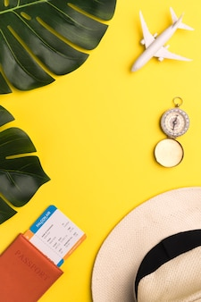 Billets, boussole et chapeau sur fond jaune