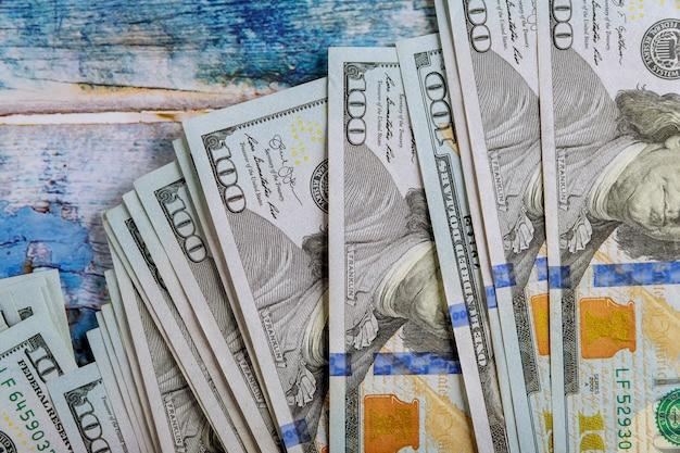 Billets de cent dollars américains d'argent dans le vieux fond en bois bleu