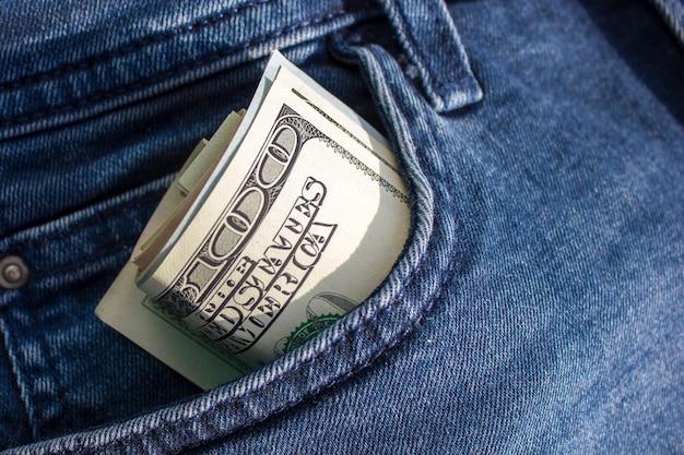 Des billets de centaines de dollars américains sont tordus dans un tube, sortant d'une poche de jeans