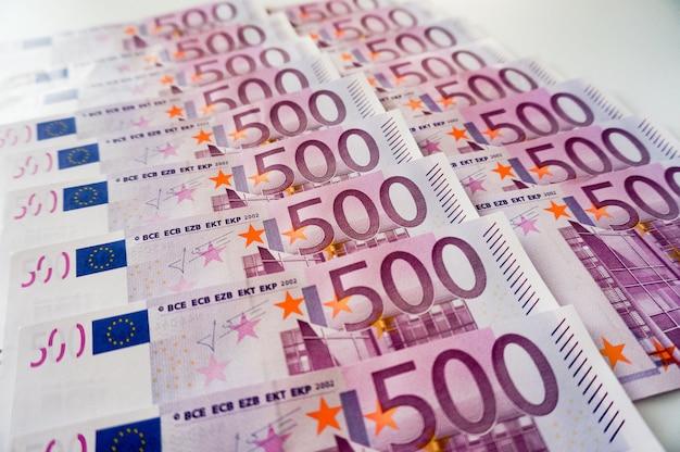 Billets de cinq cents euros sur deux rangées de fond blanc