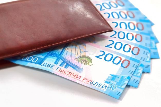 Billets de deux mille roubles russes dans un portefeuille en cuir marron sur fond blanc.