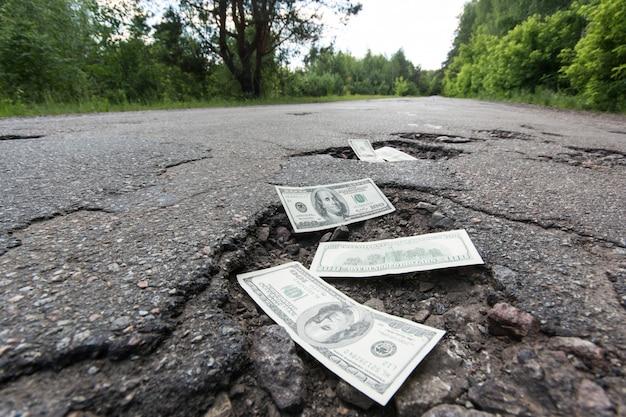 Billets d'un dollar dans les nids de poule sur la route