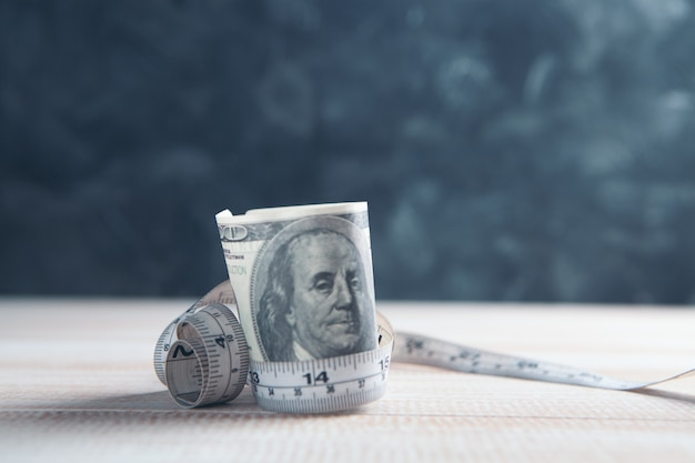 Billets d'un dollar enveloppés de ruban à mesurer