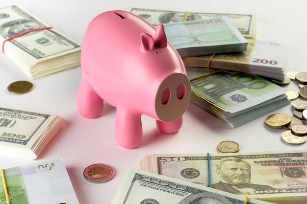 Billets d'un dollar en paquets sur un fond blanc. a proximité se trouve une tirelire sous forme de pièces de cochon rose de différents pays.