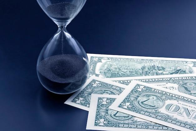 Les billets d'un dollar se trouvent près du sablier. le temps, c'est de l'argent