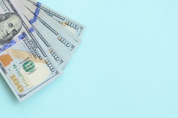 Les billets en dollars américains d'un nouveau dessin avec une bande bleue au milieu se trouvent sur un fond bleu clair