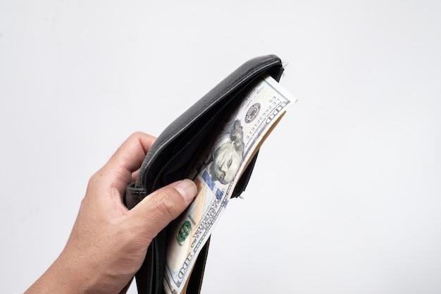 Billets en dollars américains en portefeuille noir sur fond blanc.