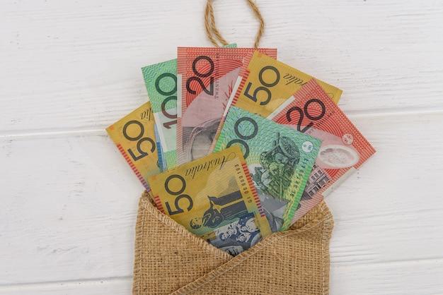 Billets en dollars australiens avec enveloppe matérielle sur fond clair