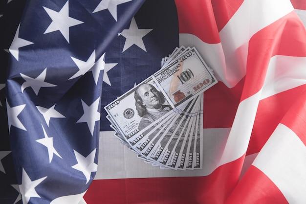 Billets en dollars et drapeau national des etats-unis.
