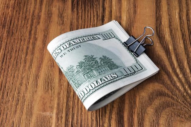Les billets en dollars sont couchés sur un fond en bois.