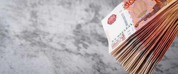 Billets en espèces russes de cinq mille roubles, le paquet est suspendu sur un fond gris.