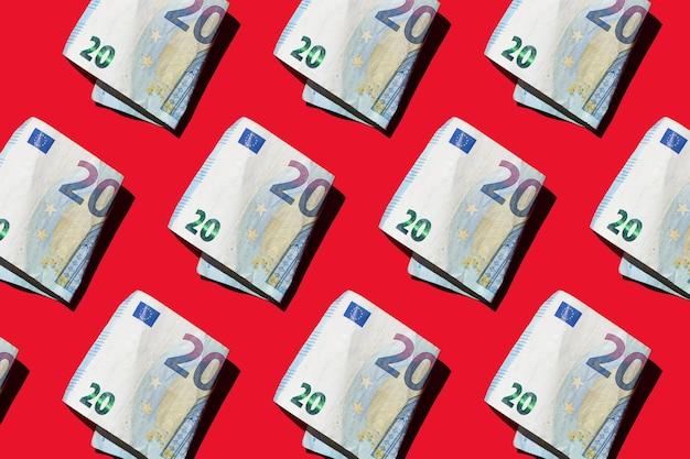 Billets d'euro de papier-monnaie sur fond rouge