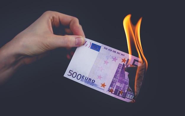 Les billets en euros brûlent sur fond noir. concept de crise mondiale au milieu de la pandémie de coronavirus.