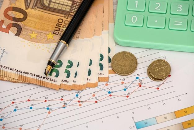 Billets en euros de concept d'entreprise avec stylo graphique et calculatrice. la finance