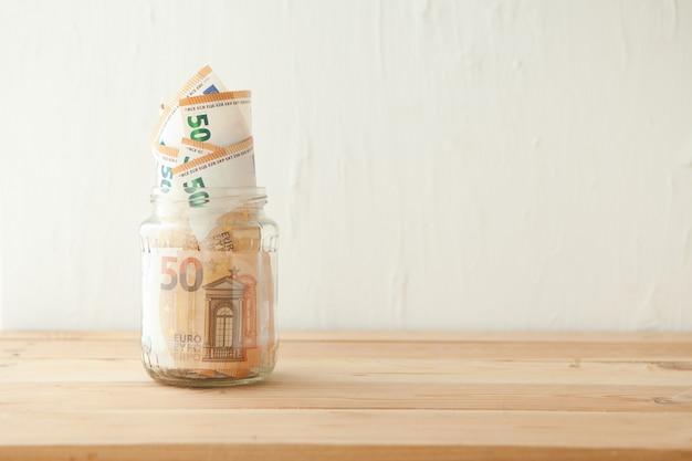 Billets en euros dans un bocal en verre au concept d'entreprise de table en bois