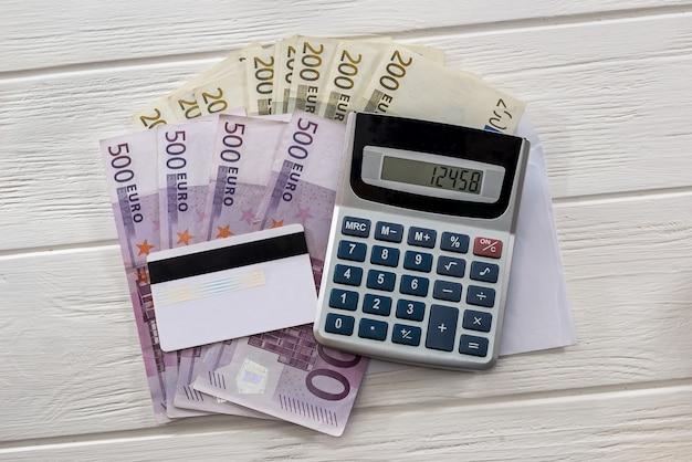 Billets en euros dans une enveloppe avec calculatrice et carte de crédit
