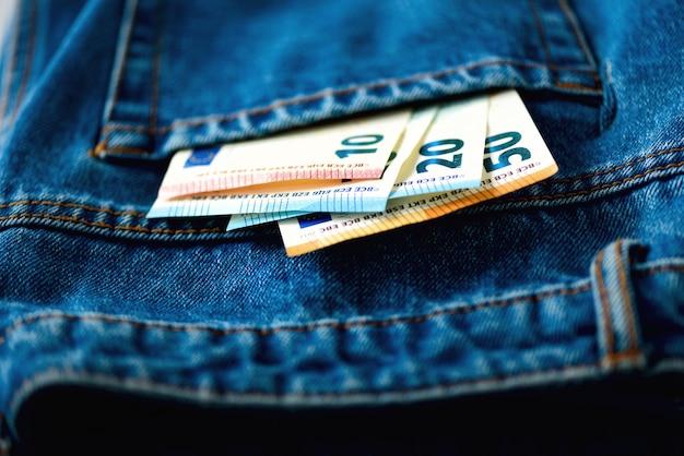Billets en euros dans la poche d'un jean.