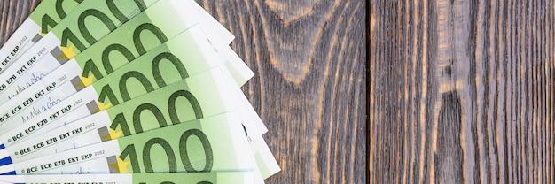 Billets en euros en éventail sur fond en bois.