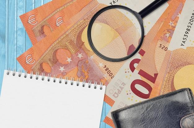 Billets en euros et loupe avec sac à main noir et bloc-notes