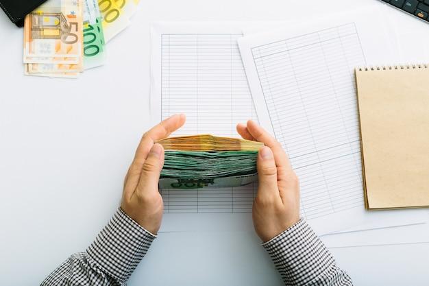 Les billets en euros sont empilés. homme faisant sa comptabilité. répartition des dépenses dans une petite entreprise. épargne, dépôt, prêt et taux d'intérêt.