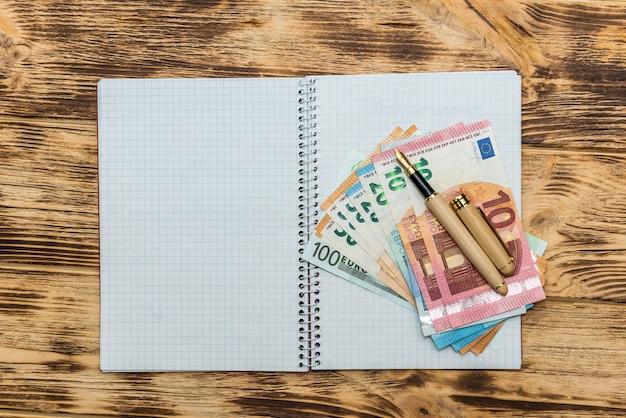 Billets en euros avec un stylo sur le bloc-notes vide