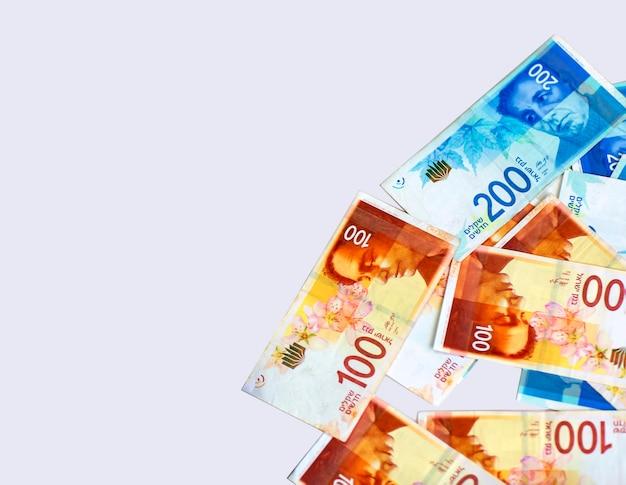 Billets israéliens new shekels sur table. monnaie sur la table. pile de nouvelles factures d'argent israéliennes d'un montant de 200 et 100 shekels. l'espace de la bannière se moque pour ajouter du texte. vue latérale avec espace de copie
