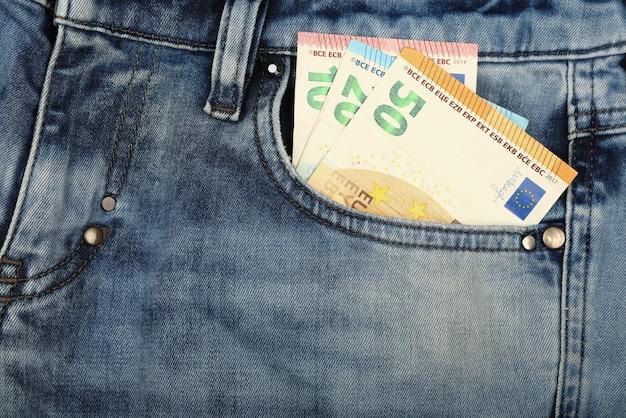 Billets en papier en euros dans la poche avant du jean