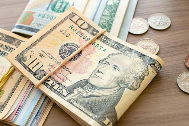 Billets et pièces en dollars américains sur des meubles en bois dans la photographie en gros plan