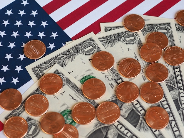 Billets et pièces en dollars et drapeau des états-unis