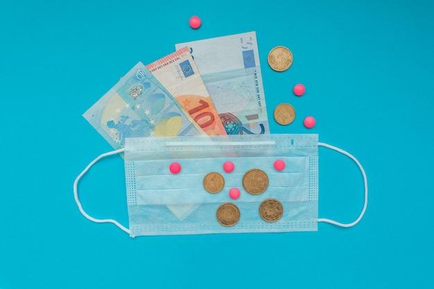 Billets et pièces en euros. masque médical et pilules roses. crise économique. frais de santé. éclosion de coronavirus.