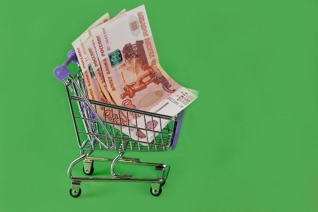 Billets rose russe dans un chariot de supermarché sur une surface verte