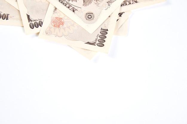 Billets de yen japonais et pièce de yen japonais sur fond blanc