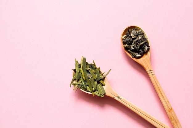 Biluochun et longjing. thé vert feuille chinoise dans une cuillère sur un fond rose.