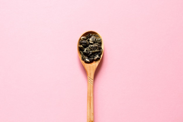 Biluochun. thé vert feuille chinoise dans une cuillère sur un fond rose.