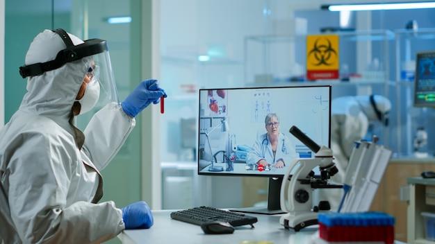 Biochimiste en combinaison expliquant à un médecin à distance l'évolution du vaccin, tenant un échantillon de sang lors d'une réunion vidéo dans un laboratoire de recherche. utiliser la haute technologie pour rechercher un traitement contre le virus covid19