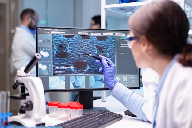 Biochimiste professionnelle analysant une expérience médicale tout en travaillant avec son équipe pour découvrir un vaccin