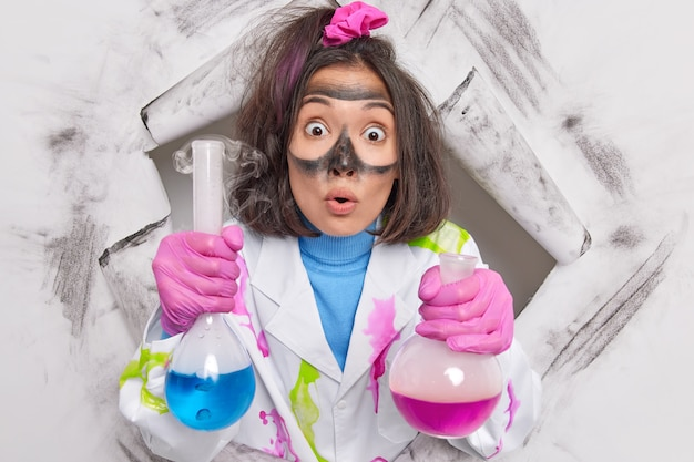 Le biochimiste scientifique travaille sur une expérience chimique tient des flacons en verre avec la solitude étant un travailleur scientifique en laboratoire vêtu d'une blouse blanche perce le trou du papier