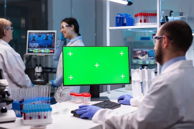 Biochimiste travaillant en laboratoire à l'aide d'un écran de maquette vert pour une expérience de biochimie avec un moniteur d'incrustation de chrominance
