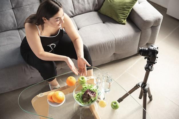 Biologique. une blogueuse caucasienne, une femme fait un vlog comment suivre un régime et perdre du poids, être positive pour le corps, manger sainement. à l'aide d'une caméra enregistrant sa préparation de salade de fruits. influenceur de style de vie, concept de bien-être.