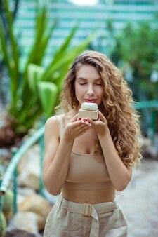 Biologique. femme aux cheveux longs en haut beige sentant une barre de savon