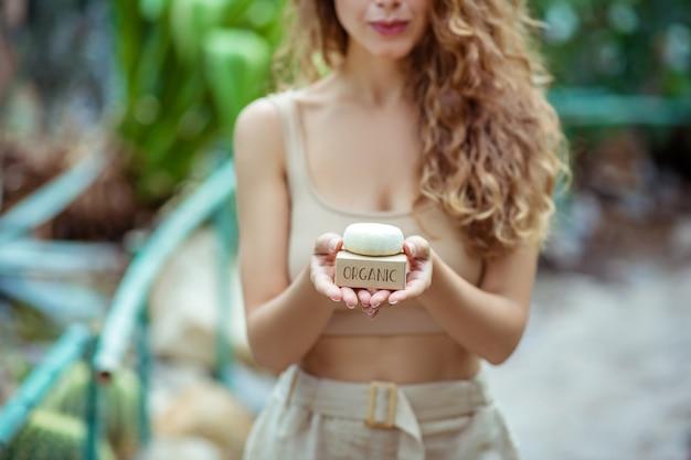 Biologique. femme aux cheveux longs en haut beige tenant une barre de savon