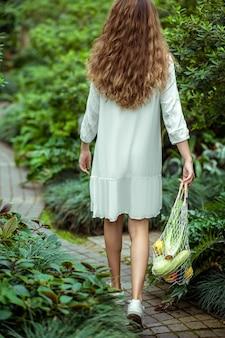 Biologique. femme en robe blanche allant et portant des sacs avec différents légumes