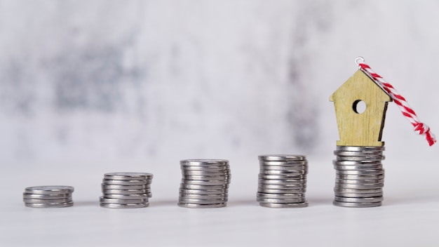 Birdhouse miniature ornement sur la pile croissante de pièces d'argent